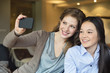Woman and her daughter taking a picture of themselves with a camera phone