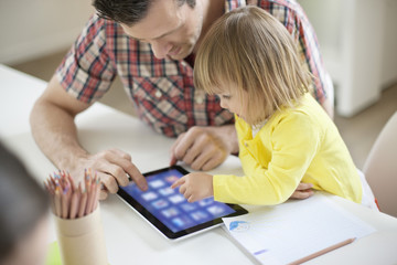Man teaching digital tablet to his daughter
