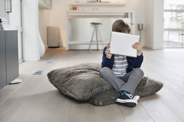 Boy hiding his face with a digital tablet