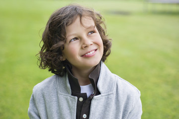 Close-up of a boy smiling in a field
