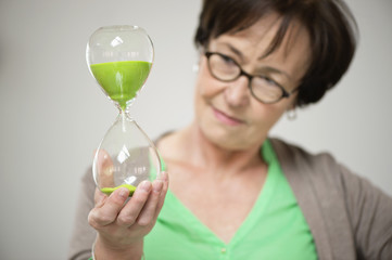 Woman looking at an hourglass