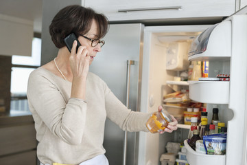 Elderly woman checking food items in a refrigerator and talking on a mobile phone