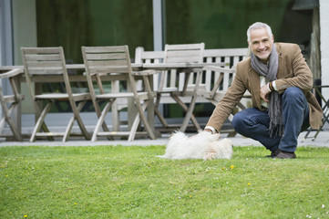 Man playing with his pets in a garden