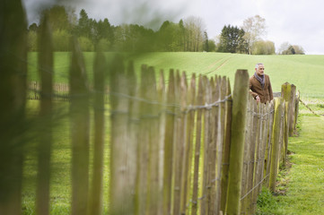 Man standing by fence in a field