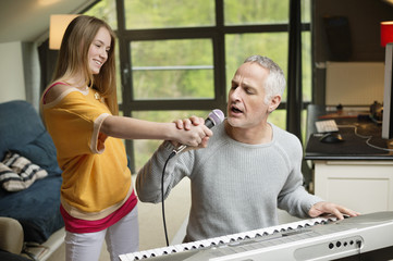 Man singing and playing a piano with his daughter at home