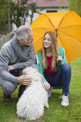 Man with his daughter pampering a dog in a lawn