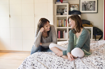 Woman with her daughter smiling in the bedroom