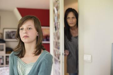 Woman watching her daughter behind the door in the bedroom
