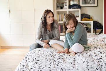 Woman scolding her daughter in the bedroom