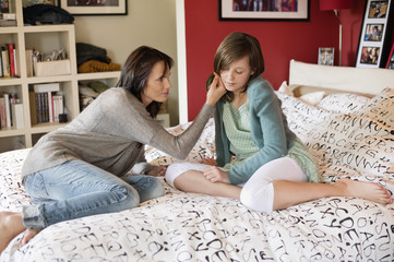 Woman consoling her sad daughter in the bedroom