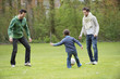 Boy playing soccer with two men in a park