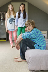 Teenage boy with his two sisters at home