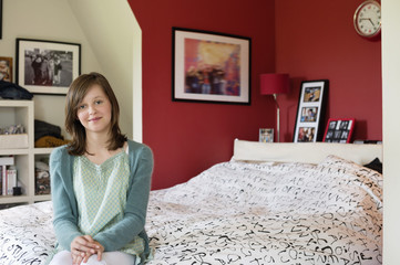 Portrait of a girl sitting on the bed and smiling