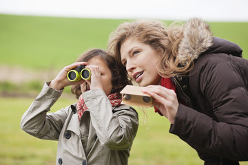 Boy looking through binoculars standing with his mother