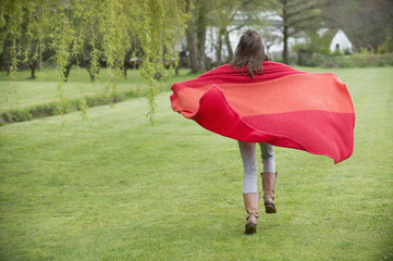 Girl running in a field with a blanket