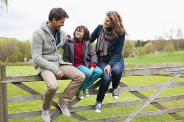 Boy sitting with his parents on the gate of a cottage