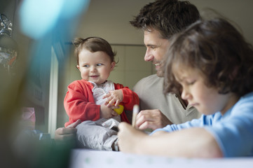 Close-up of a man with his children at home