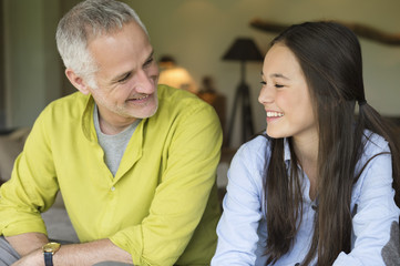 Man and his daughter smiling at home