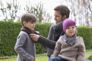 Man putting on warm clothing to his children