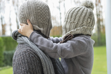 Man and son covering their faces with hats