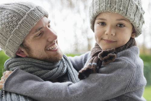 Man carrying his son in a park