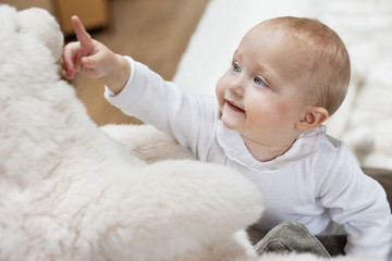 Close-up of a baby girl playing with a teddy bear
