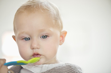 Close-up of a baby girl holding a spoon