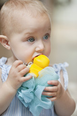 Close-up of a baby girl playing with a toy