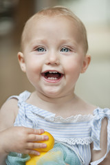 Close-up of a baby girl playing with a toy and laughing