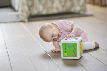 Baby girl playing with a musical block toy