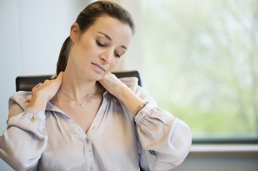 Close-up of a businesswoman suffering from neckache