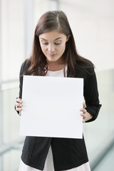 Businesswoman holding a blank placard in an office