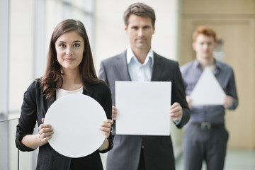 Business executives holding blank placards in an office