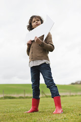 Boy holding an arrow sign in a field
