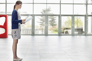Businesswoman holding documents and standing in an office lobby