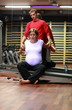 Physical therapist stretching ,pregnant woman's arms in gym