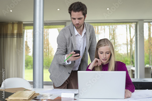 Woman working on a laptop with a man using mobile phone beside her
