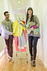 Fashion designers walking in a corridor with clothes rail