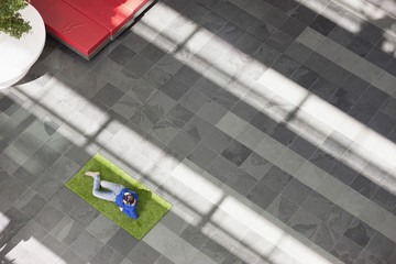 Businessman relaxing on grass in an office lobby