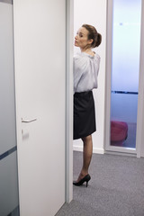 Businesswoman peeking through a door in a corridor