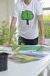 Plant and environmental awareness poster on a table in front of a man