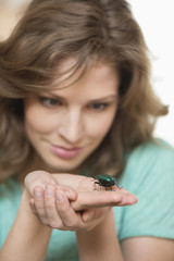 Woman looking at a beetle on her hands