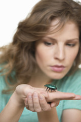 Woman looking at a beetle on her hand