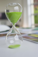 Close-up of an hourglass with green sand in it