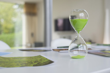 Green hourglass and ecological poster on a table