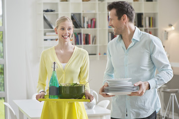 Couple carrying plates and food for serving