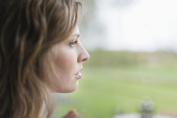 Woman looking through the glass of window