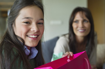 Girl holding a shopping bag and smiling with her mother