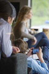 Boy using phone with his sister and mother at home