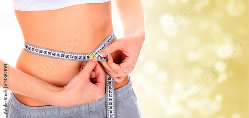 Woman taking measurements of her body on blurry background